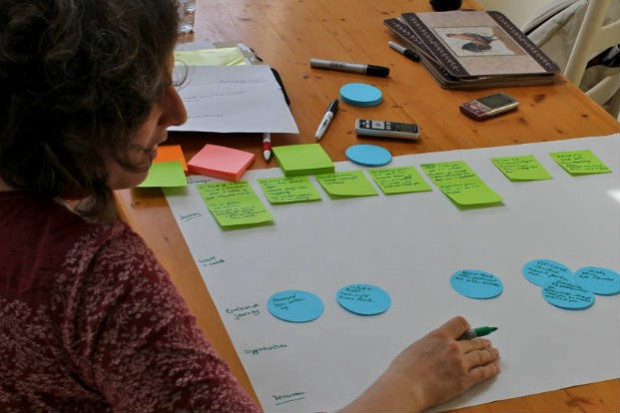 Picture shows a researcher helping to fill out a user research exercise at a kitchen table