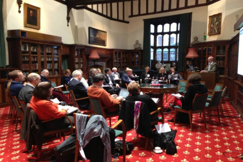 Photo of older people participating in a workshop in a wood-panelled room
