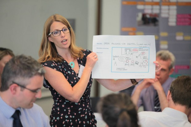 A facilitator holds up and talks through an A3 poster titled 'open policing - via digital' with a diagram of the digital process and relationships.