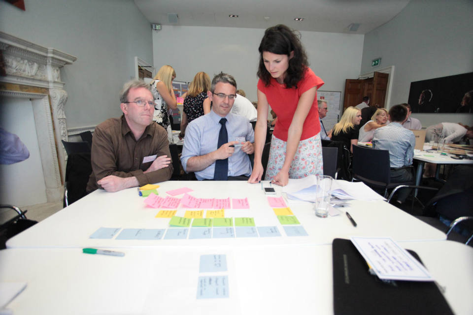 A woman stands over a table, working with two seated men - they are discussing the colour-coded post-its on a flipchart sheet in front of them.