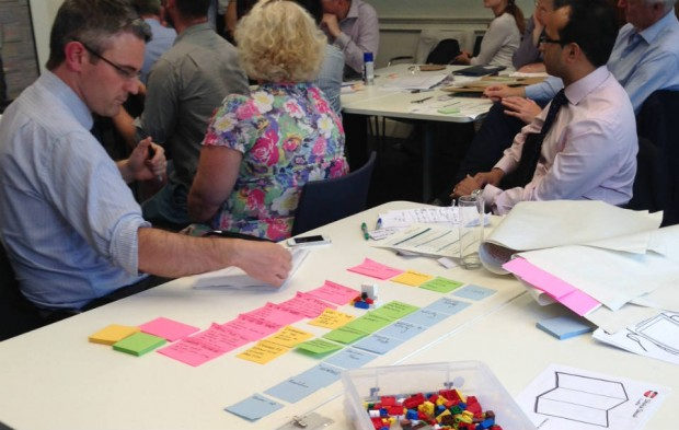 A man is sitting at a table, concentrating on writing on post-it notes that are lined up by colour. On a table behind him a group of people are listening to a speaker. There is a box of lego on the table.