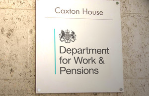 A sign mounted onto the wall of a stone building reads 'Caxton House', 'Department of Work and Pensions'