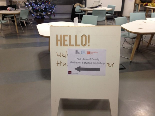 A sandwich board is set up on the floor with a paper sign on it saying 'hello' and pointing people into the workshop room.