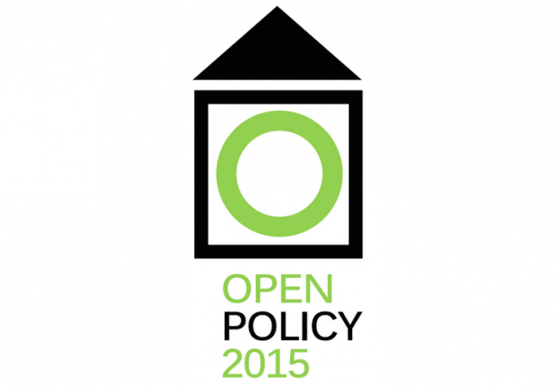 The Open Policy 2015 logo is a black triangle pointing upwards over a black-outlined square with a green circle within. Underneath it says Open Policy 2015 in green and black.
