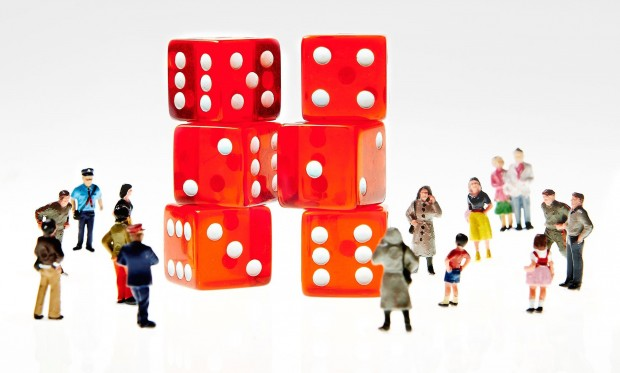 Small figurines of people standing around two towers made up of red dice