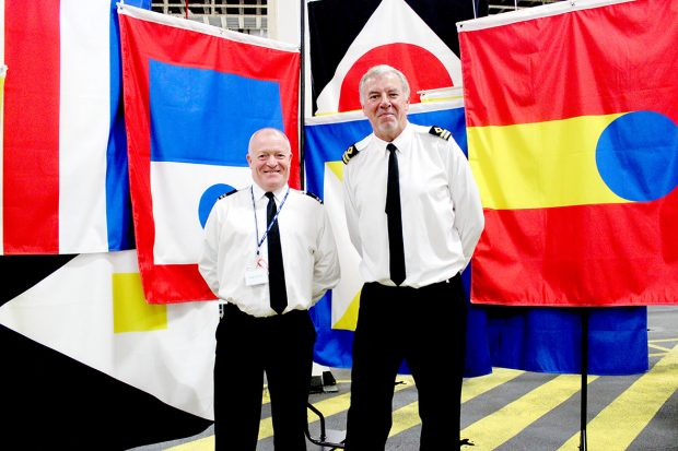 This is an image of marine vexillologists, flag experts, in front of the speculative flag installation by Policy Lab onboard the RFA Lyme Bay ship at London International Shipping Week 2019.